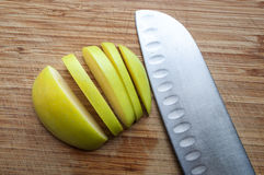 Large knife and apple on a wooden board Stock Images