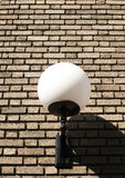 Large lamp on a brick wall Stock Images