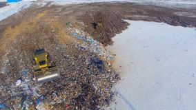 A large landfill site with two operating compactors tractors. A city landfill with two working compactors that scare away bird flocks stock video footage