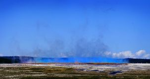 Large Landscape in Yellowstone with Steam Rising and People to Give Scale. Large lanscape in Yellowstone National Park with steam rising and huge cloud people to royalty free stock photography