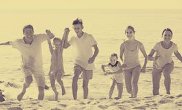 Large laughing family on beach on sunny day Royalty Free Stock Photography