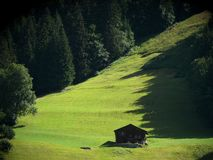 Mountain hut in green meadow royalty free stock photos