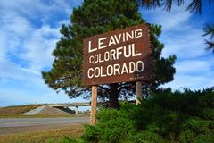 Large Leaving Colorful Colorado Wooden Roadside Highway Sign on a Sunny Day stock photo