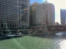A large leisure boat docked on riverwalk of Chicago River with recreation & leisure seekers covered by colorful sunbeams in Chicag stock photography