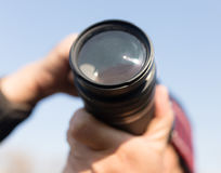 A large lens in the camera of a man.  stock photos