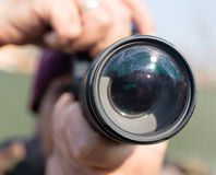 A large lens in the camera of a man.  Stock Images