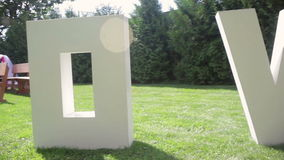 Large letters LOVE on the grass on wedding stock video