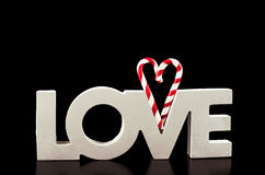 Large letters LOVE and Heart Lollipop isolated on black - Stock Stock Photos