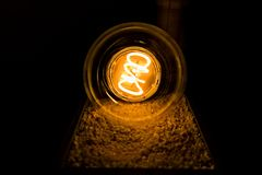 Large light bulb at night. Large light bulb on a tray with white gravel at night royalty free stock photo