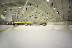 Large light indoor ice rink. People, service personnel, polished ice Royalty Free Stock Image