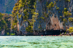 Large limestone rock with cave and tourist canoeing in Phang nga Royalty Free Stock Image