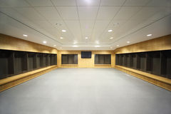 Large locker room. Large clean locker room. gray floor and ceiling, big televisor on wall stock photography