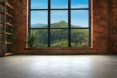Large Loft Interior With Mountains In The Window. Large Loft Interior With Concrete Floor And Brick Walls With Mountains In The Window Stock Photography