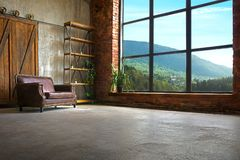 Large Loft Interior With Mountains In The Window. Large Loft Interior With Concrete Floor And Brick Walls With Mountains In The Window Royalty Free Stock Photography