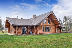 Large log cabin house exterior with grass filled back yard. Stock Photos