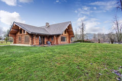 Large log cabin house exterior with grass filled back yard. Royalty Free Stock Photos