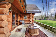 Large log cabin house exterior with patio area. Royalty Free Stock Photo