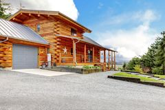 Large log cabin with porch and garage. Royalty Free Stock Images