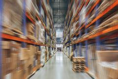 Large Logistics hangar warehouse with lots shelves or racks with pallets of goods, perspective with motion blur effect stock photo