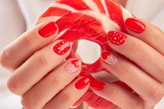 Large lollipop in manicured hands. Woman hands with red manicure holding red and white tasty lollipop Stock Photo