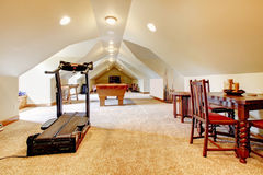 Large long attic game room with tv, pool and sport equipment. Royalty Free Stock Images