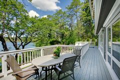 Large long balcony home exterior with table and chairs, lake view. Royalty Free Stock Photo