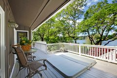 Large Long Balcony Home Exterior With Hot Tub And Chairs, Lake View. Royalty Free Stock Photos