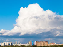 Large low cloud in blue sky over town in summer Stock Photography