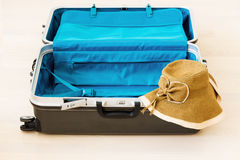 Large luggage and wicker hat on white wooden background. Stock Photo