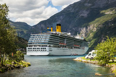 Large luxury cruise ship in Norway fjords. View over a large luxury cruise ship anchored in a fjord in Norway, as seen from the camping site next to the water Royalty Free Stock Image