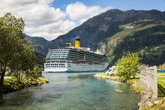 Large luxury cruise ship in Norway fjords. View over a large luxury cruise ship anchored in a fjord in Norway, as seen from the camping site next to the water Stock Photo