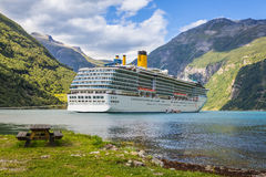 Large luxury cruise ship in Norway fjords. View over a large luxury cruise ship anchored in a fjord in Norway, as seen from the camping site next to the water Royalty Free Stock Photography