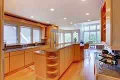 Large luxury modern wood kitchen . Large luxury modern wood kitchen with granite counter tops and yellow hardwood floor royalty free stock images
