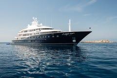 Large luxury motor yacht. Anchored near rocky island Stock Image