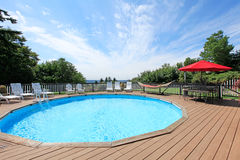 Large luxury round pool with many sun chairs on wood deck. Stock Images