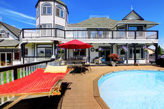 Large luxury round pool with many sun chairs on wood deck and red hamock. Stock Photography