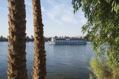 Large egyptian river cruise boat sailing on Nile. Large luxury traditional Egyptian river cruise boat sailing on the Nile framed by trees stock photography