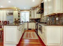 Large luxury white kitchen with cherry hardwood. Stone tiles and stainless steal appliances Stock Image