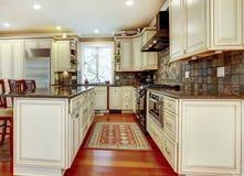 Large luxury white kitchen with cherry hardwood. Stock Image