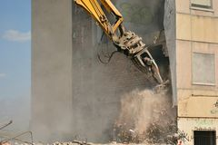 Arm of machine demolishing an apartment building royalty free stock photography