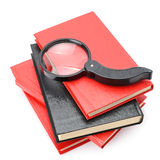 Large magnifier on book stack Stock Photo