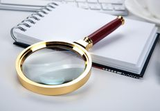 Large magnifying glass lies on a notebook on the desktop. Closeup Royalty Free Stock Image