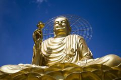 A large figure of a seated golden buddha. A large, majestic and beautiful figure of a seated golden buddha on the blue cloudy sky background Royalty Free Stock Photography