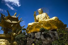 A large figure of a seated golden buddha. A large, majestic and beautiful figure of a seated golden buddha in Dalat, Vietnam on the blue cloudy sky background Stock Images