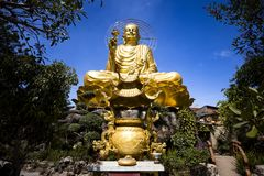 A large, majestic and beautiful figure of a seated golden buddha. In Dalat, Vietnam on the blue cloudy sky background Royalty Free Stock Photo