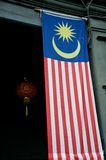 Large Malaysia flag hangs in doorway with red Chinese lantern in back. Penang, Malaysia - January 15, 2016: A large Malaysia flag drapes in an entrance with a Stock Images