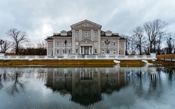 Large mansion or house stands on the former site of the fortress with a moat. Front of the house is reflected in the water Stock Image