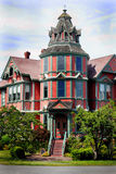 Large Mansion. Street view of a beautiful large old luxurious victorian home with lots of gingerbread trim, a turret and a lot of windows royalty free stock image