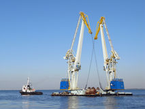 Large maritime cranes and boat. Working in the river Stock Photos