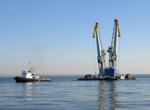 Large maritime cranes towed by boat Royalty Free Stock Photography